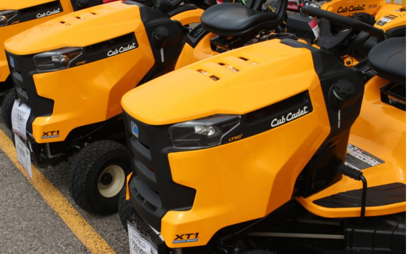 Bunch of cub cadet mowers sitting in yellow on a driveway for a piece on mower brands to avoid