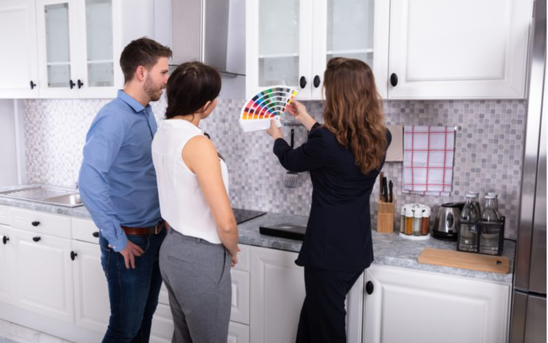 Professional designer showing a biracial couple various options of cabinets and colors that affect kitchen remodeling costs