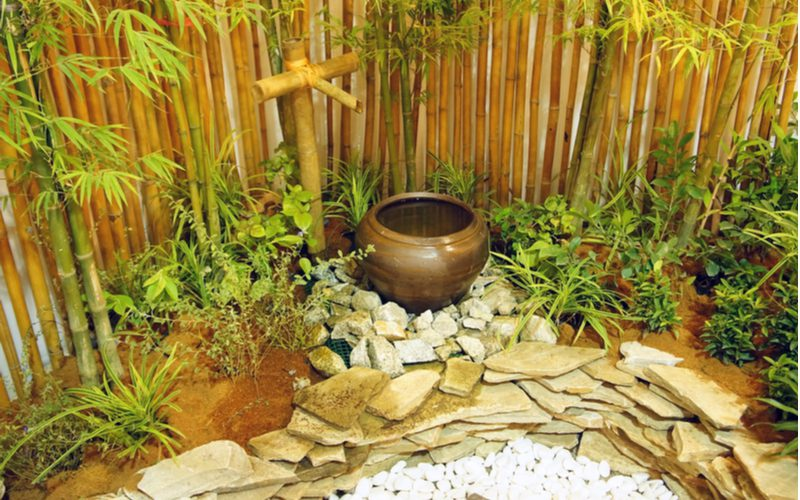 Zen garden with privacy plants made of bamboo next to a koi pond