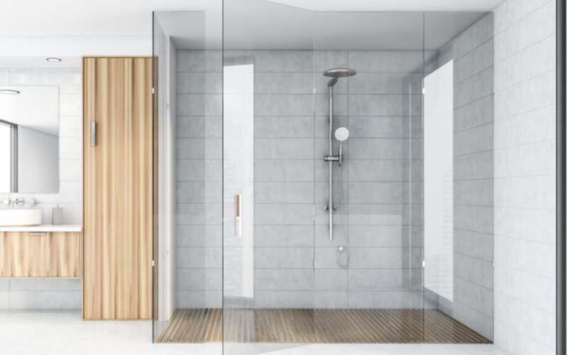Bathroom idea featuring a giant glass walk-in shower with a rain shower head next to a modern bamboo vanity and linen closet