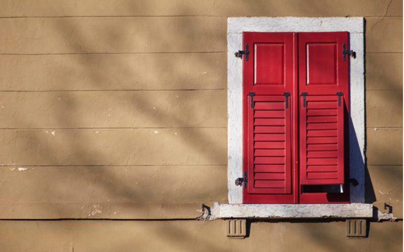For a piece on what do plantation shutters cost, red wooden shutters sit closed on a window on a brown house