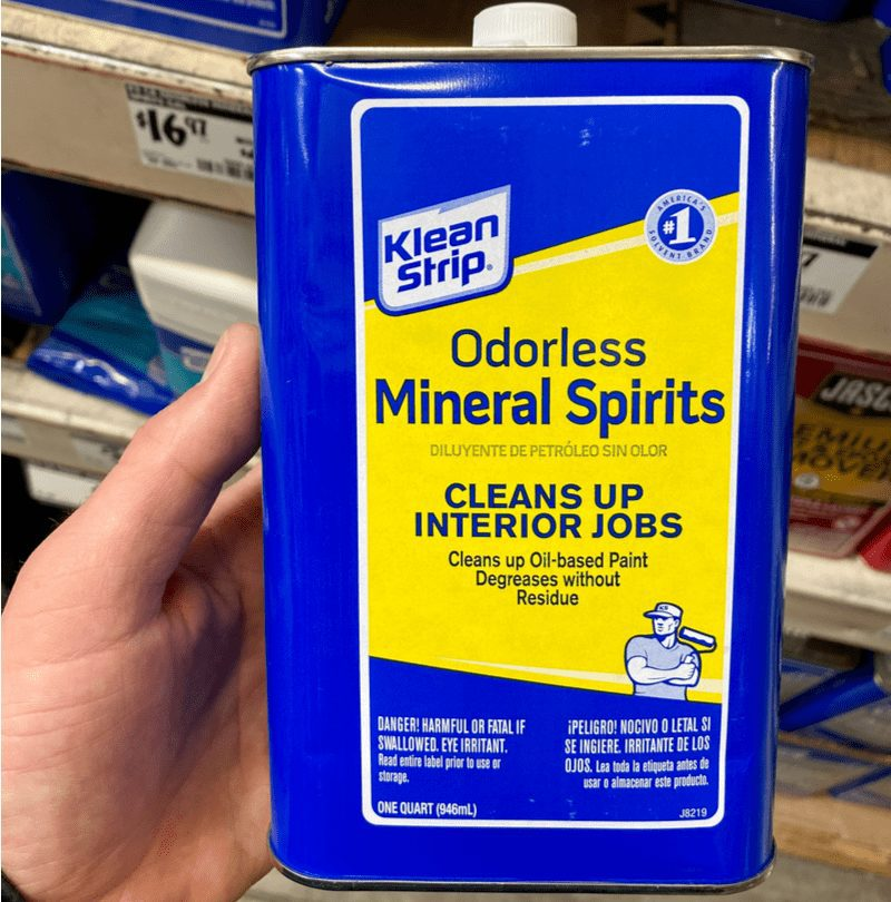Person holding a mineral spirits can in their left hand for a piece on removing paint from metal
