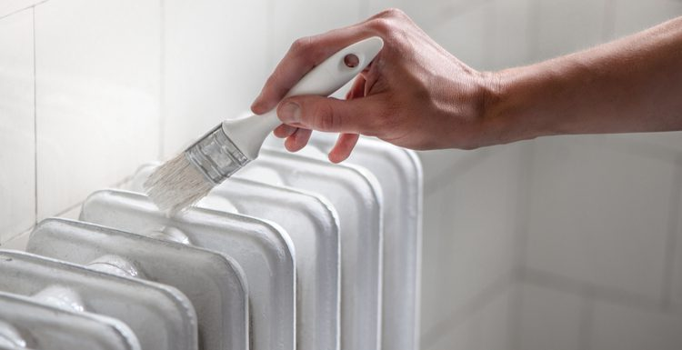 For a piece on how to paint aluminum, a woman holds a paint brush and paints an aluminum radiator