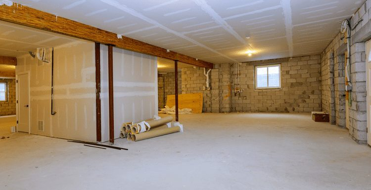 For a piece on how to finish a basement, a largely unfinished basement sits with materials stacked up and the middle section taped and drywalled