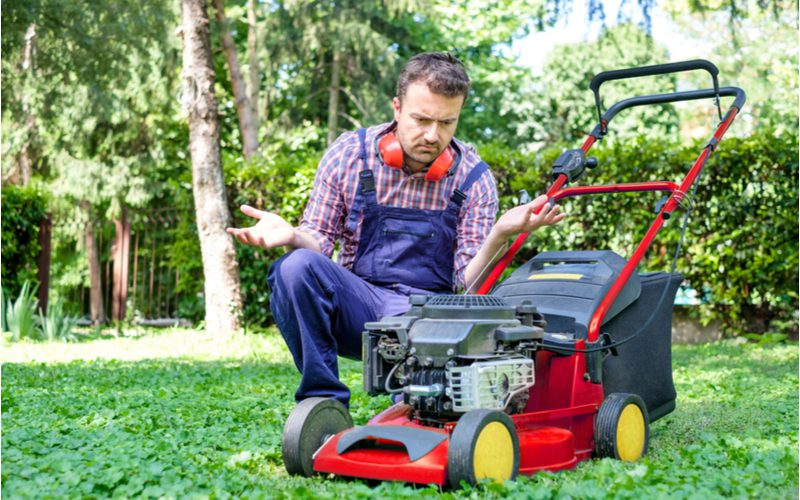 Man upset because his lawn mower is broken and he didn't read our guide on lawn mower brands to avoid