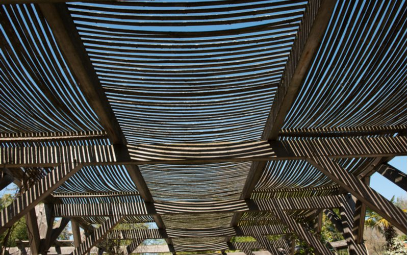 Bamboo slats sit on a wooden frame as a unique patio shade idea