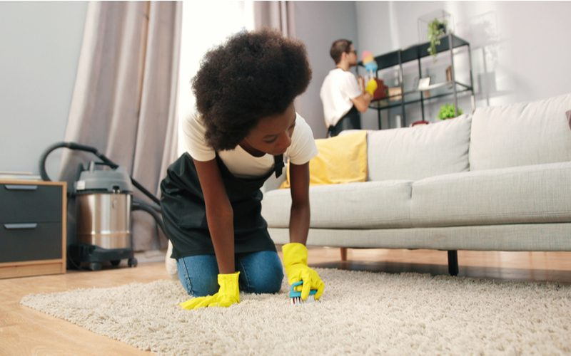 Woman on her hands and knees looking at carpet