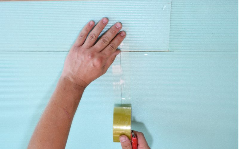 Piece on how to install laminate flooring featuring a person taping soundproofing subfloor that'll go below the lamimate