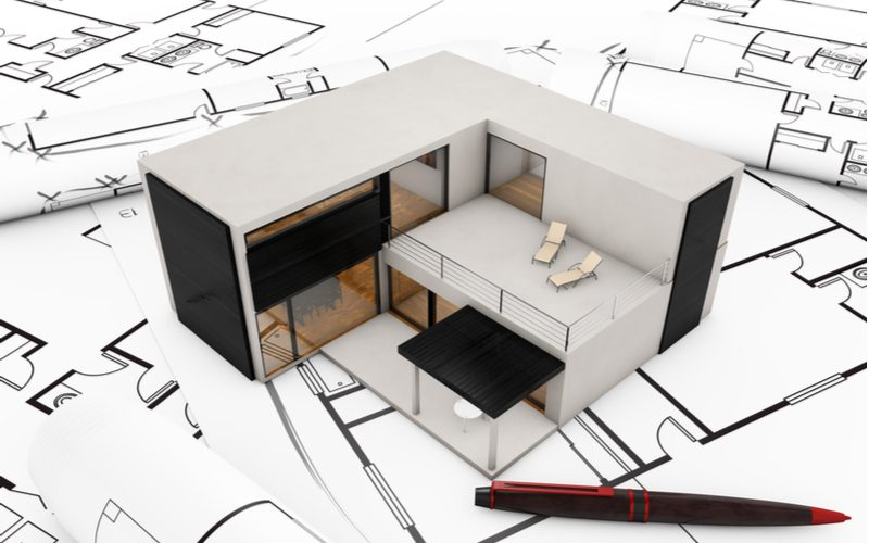 For a piece on modular home prices, a tiny model modular home sits on a black and white blueprint