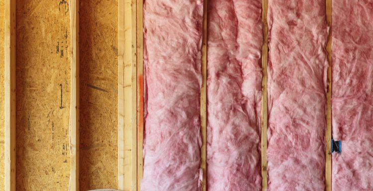Image showing unfaced insulation in an open studded wall for a piece on faced vs unfaced insulation