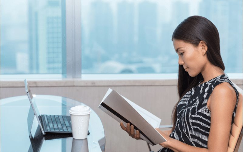 For a piece on what happens if you fail the real estate exam, a young Asian woman reading a book and studying to pass the next time in a highrise building