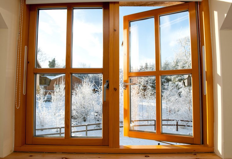 Cool early morning after a frosty winter snow for a piece on best replacement windows showing wooden framed window