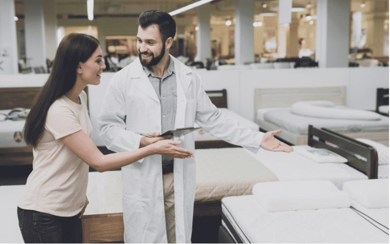 Woman walking through a mattress store with a doctor in a white coat