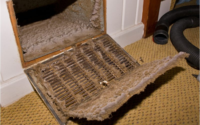 Extremely dirty air vent in a home with dust buildup to symbolize why you should regularly change your furnace filter