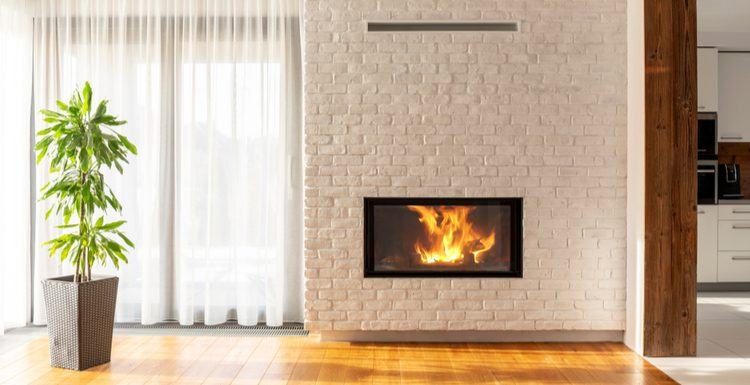 Featured image for a post on standard fireplace dimensions featuring a brick mantle and chimney inside which sits a fully-enclosed gas fireplace