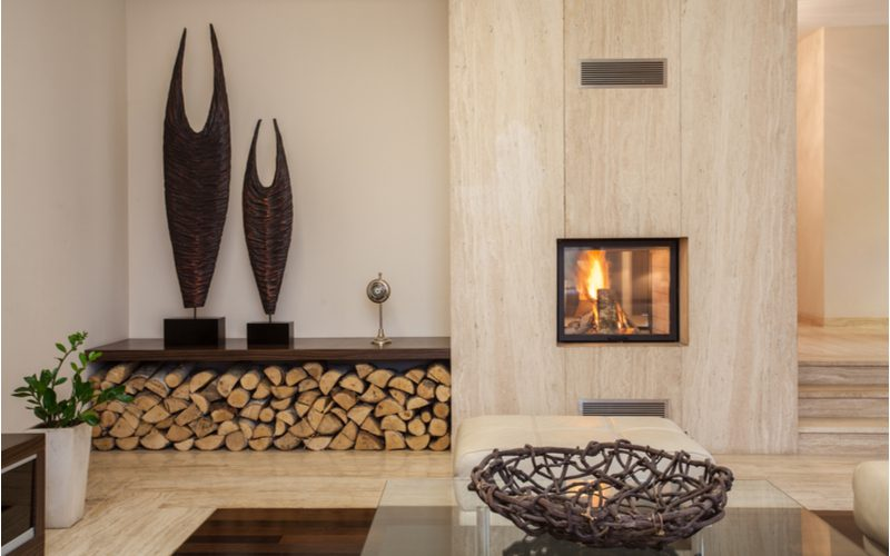 Living room with fireplace and wood nook and Mexican-style resort decorations and floor to ceiling chimney paneling