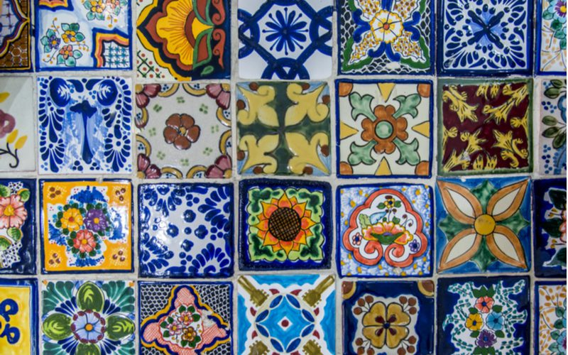 Pretty and colorful tiles laid out in a row to highlight a key design trait of Mexican kitchens