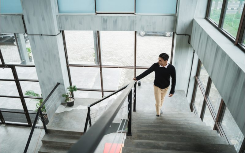 Asian businessman walking up a concrete staircase with metal cable trim for a piece on stair trim ideas