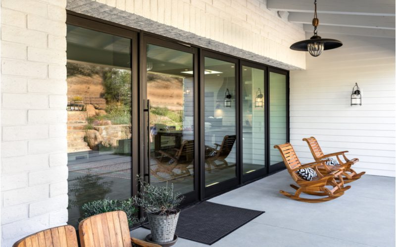 Front porch design featuring five giant floor to ceiling windows that brings the interior of the home outside