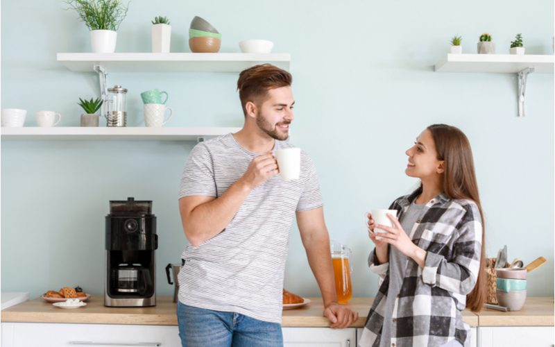 For a piece on coffee station ideas, a young couple standing together drinking cups of coffee in front of their coffee maker