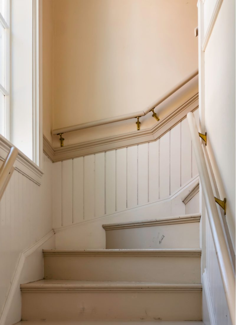 Wainscoting idea in a stairway with vertical molding halfway up the wall below the railing