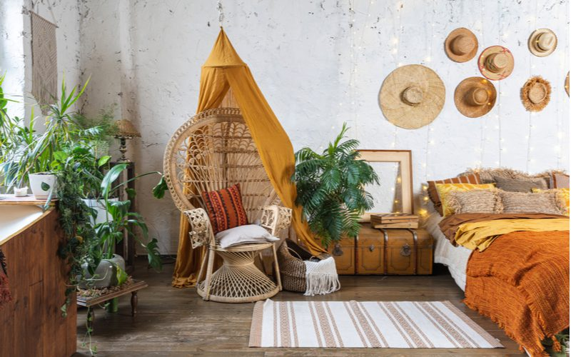 As an image for a piece on boho curtains, a living room in such a style with a bed and lots of hats mounted on the wall