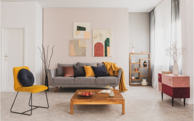 Grey couch living room idea with lots of bright colored pillows and natural wood furniture