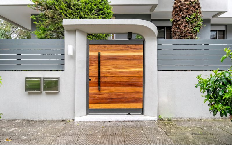 Fence gate house entrance idea with a metal fence with a natural wood entry door