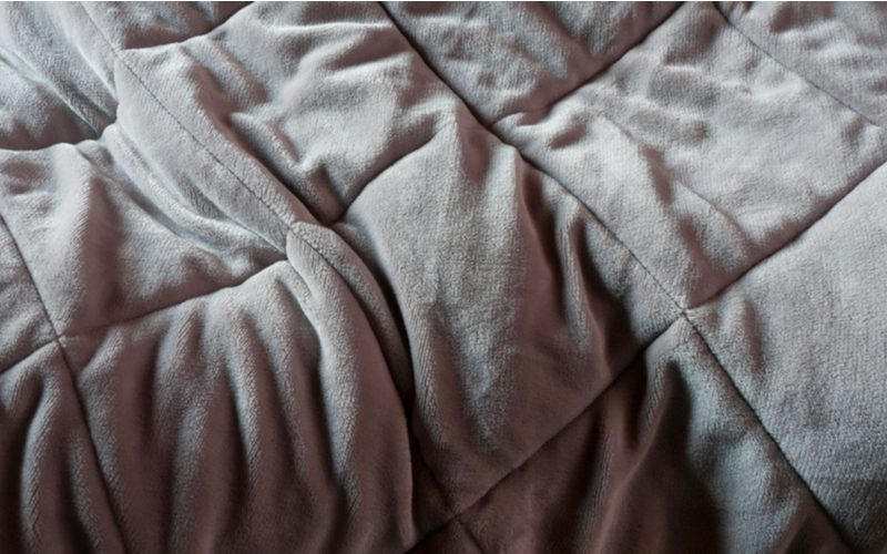 Weighted type of blanket laid out on a bed in grey color and slightly wrinkled