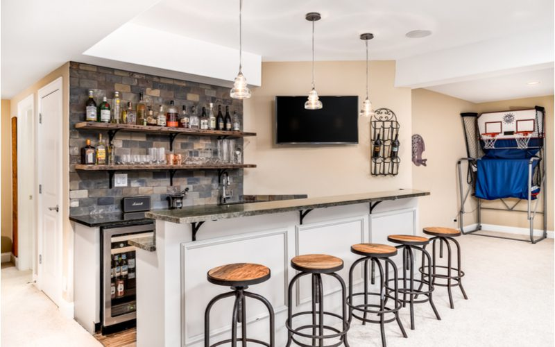 Real life example of a basement bar idea with a basketball hoop machine next to the bar which is in front of lots of liquor bottles with natural stone and wood finishes