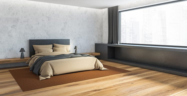 For a piece titled What Size Rug Under a King Bed, a king bed sits on an orange-brown rug in the corner of a bedroom overlooking a cityscape