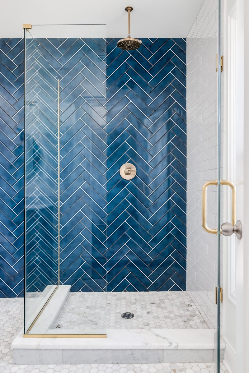 Blue walled tile shower idea in a herringbone pattern with glass walls on two sides with a rain showerhead above
