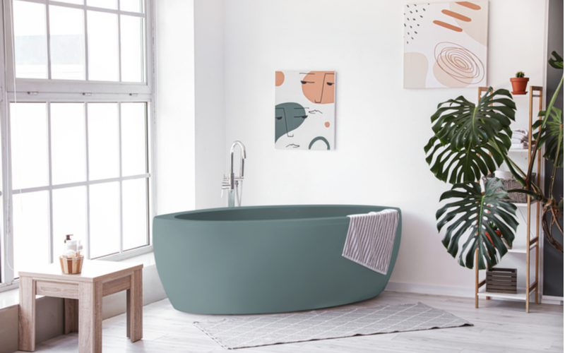 For a roundup on grey tile bathroom ideas, a grey above-ground tub with chrome fixtures and very light grey wood-look floor tiles and white walls with colorful art made of earth tones