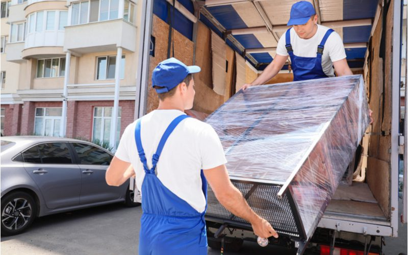 Two men in white shirts with blue overalls and hats pulling a well-wrapped black metal shelf from a truck for a piece on whether or not you should tip furniture delivery men