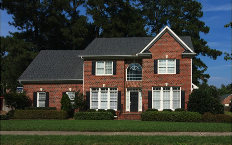 Example of the various types of siding featuring a brick sided home with big windows in the popular Colonial style