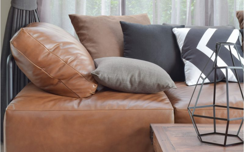 Dark brown couch living room idea to play with different textures and patterns of pillows