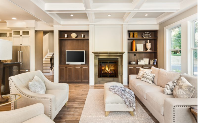 Living room with fireplace built for entertaining with lots of white furniture in the middle above a rug