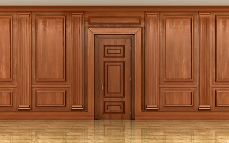 For a piece on how to paint wood paneling, a big wooden door sits in the middle of wood wood panels