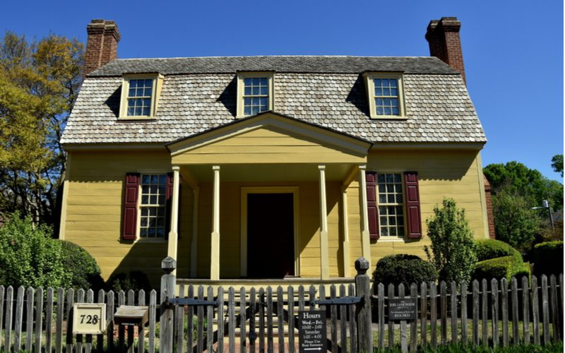 Gorgeous yellow home with dormers in the Gambrel roof shown from the front entrance