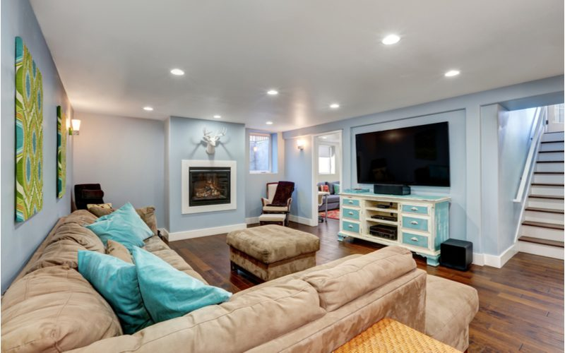 Natural light in a basement with dark wooden flooring and blue walls and white trim
