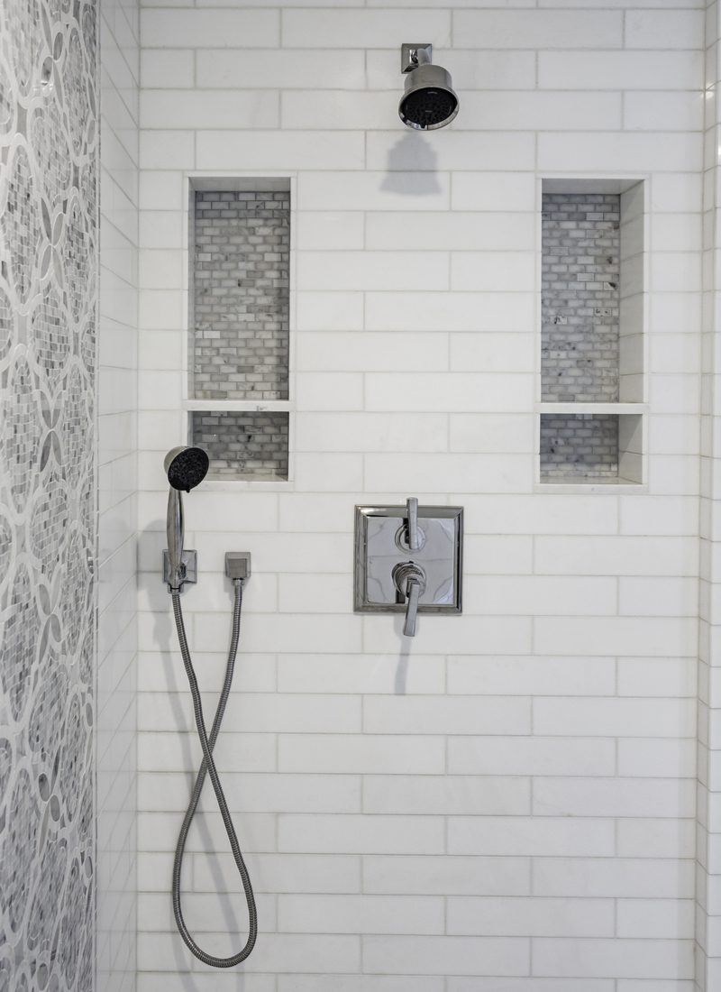As an example of the best tile shower ideas, a subway tile shower with two large soap shelves on either side of the head and faucet with a spanish-style grey tile accent wall