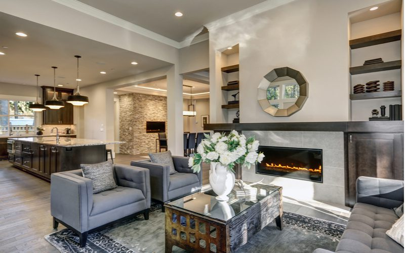 Chic-decorated living room with fireplace just off the kitchen in neutral earth tones