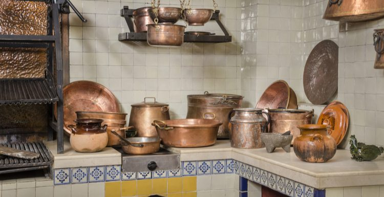 Lots of pots and pans in a white and blue and yellow tiled kitchen for a piece on Mexican Kitchens