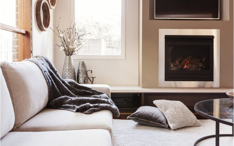 Warm comfy blankets draped on a couch next to a fireplace in a living room