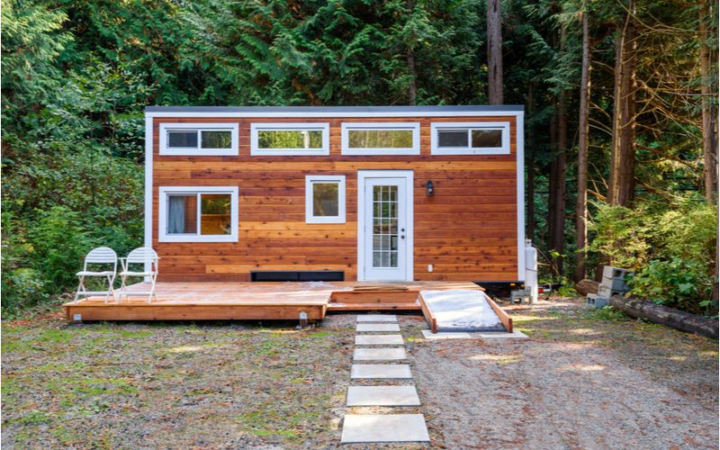 Image of a small wooden tiny house sitting outside a heavily forested backyard