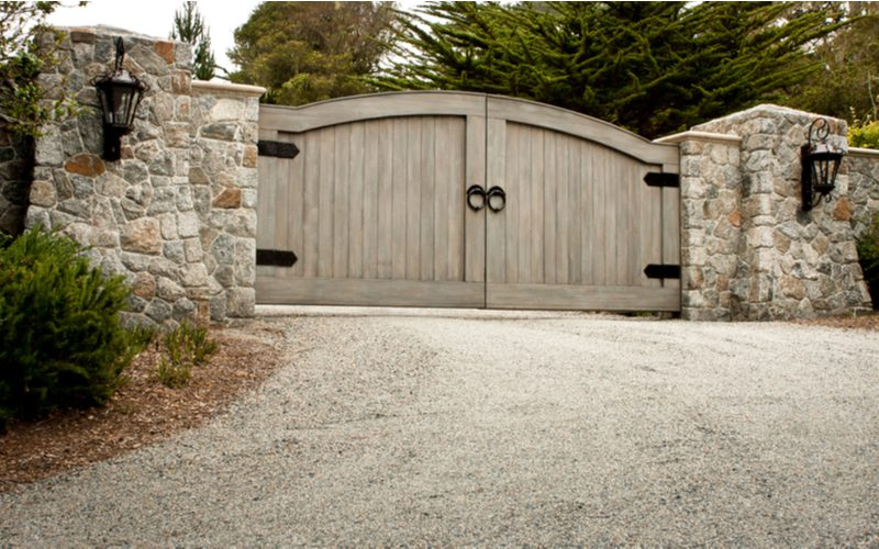 Double door wooden driveway gate idea with black farmhouse-style hardware