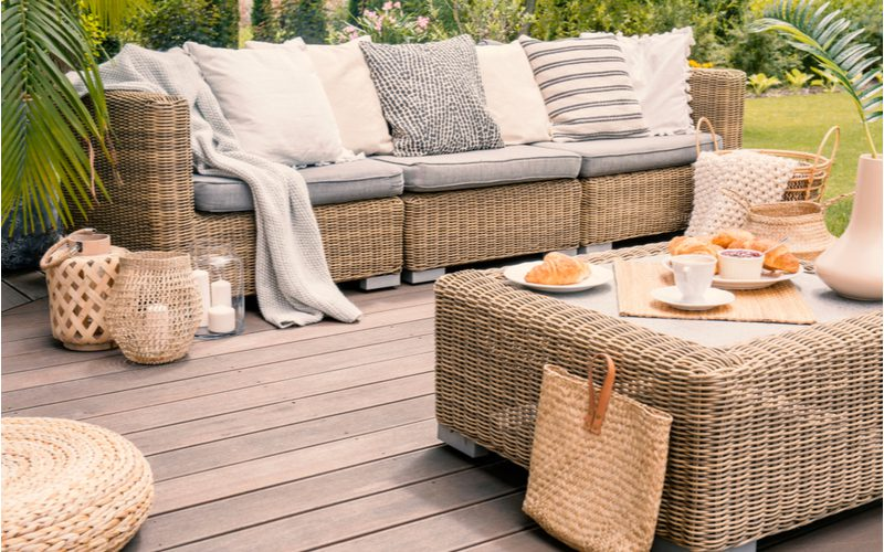 Wicker patio furniture sitting on a light grey wooden deck with new foam cushion replacements just added to the set to change the look