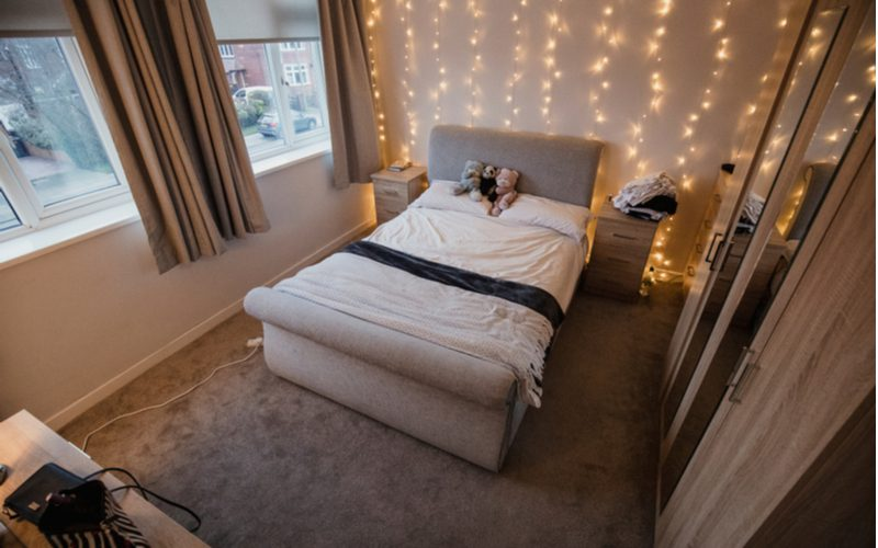 For a piece on dorm room ideas, a modern and small white dorm room with curtain lights hang from the ceiling