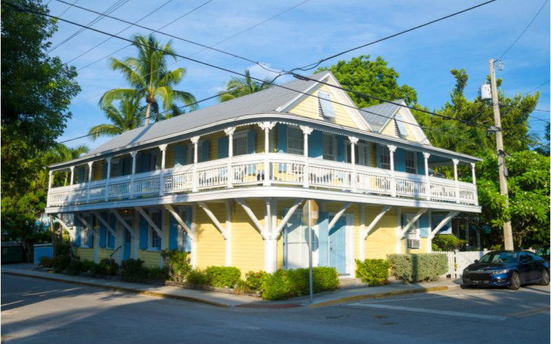 For a piece on porch overhang and roof ideas, an overhang below a wraparound porch on a yellow home in Key West