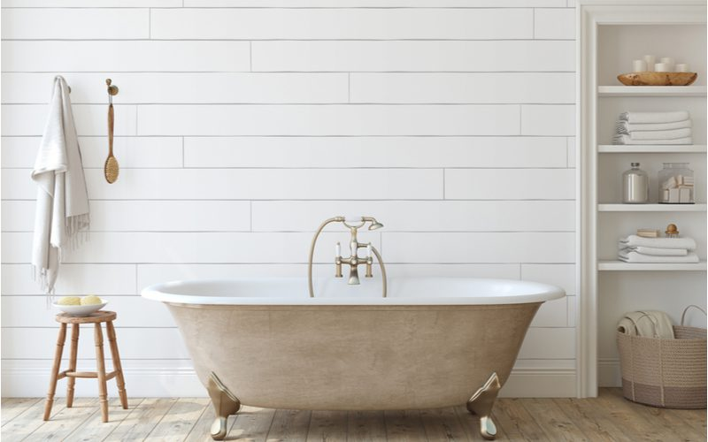 Bathroom full of farmhouse decor with a white shiplap wall, a light brown barnwood floor, and white shelves and wooden fixtures